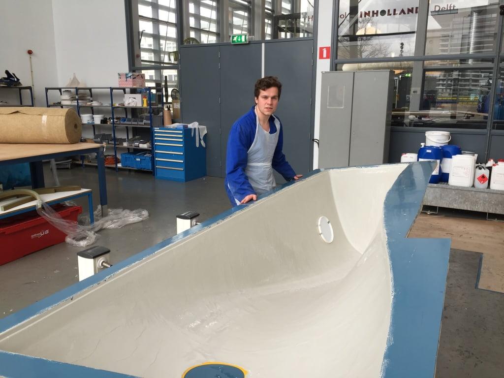 Student Martijn van Meijel in het Composietenlab van Inholland bij de bank-in-wording omgekeerd in de mal. Hierna wordt de bank met Miscantus-beton afgevuld.